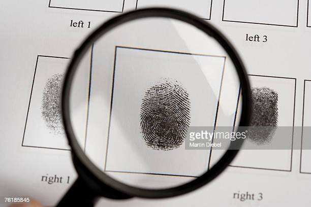 A magnifying glass above a fingerprint document