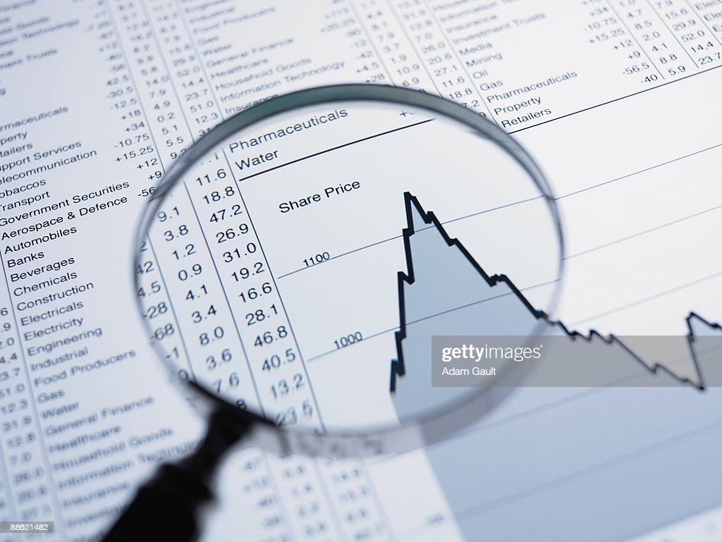Magnifying glass and descending line graph and list of share prices : Stock Photo