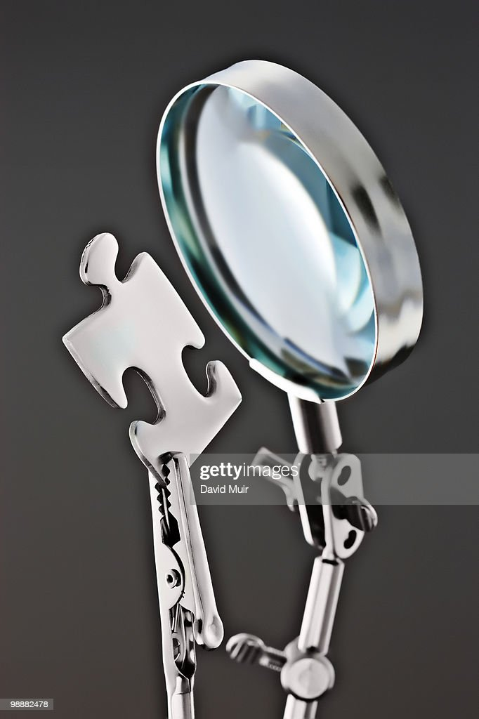 magnifying glass and puzzle piece : Stock Photo