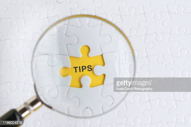 magnifying glass and tips text on puzzle piece - stunt stock pictures, royalty-free photos & images