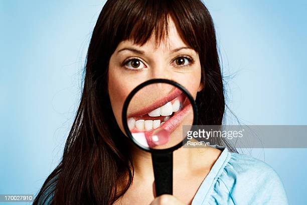 Magnifying glass distorts mouth of cute young woman bizarrely