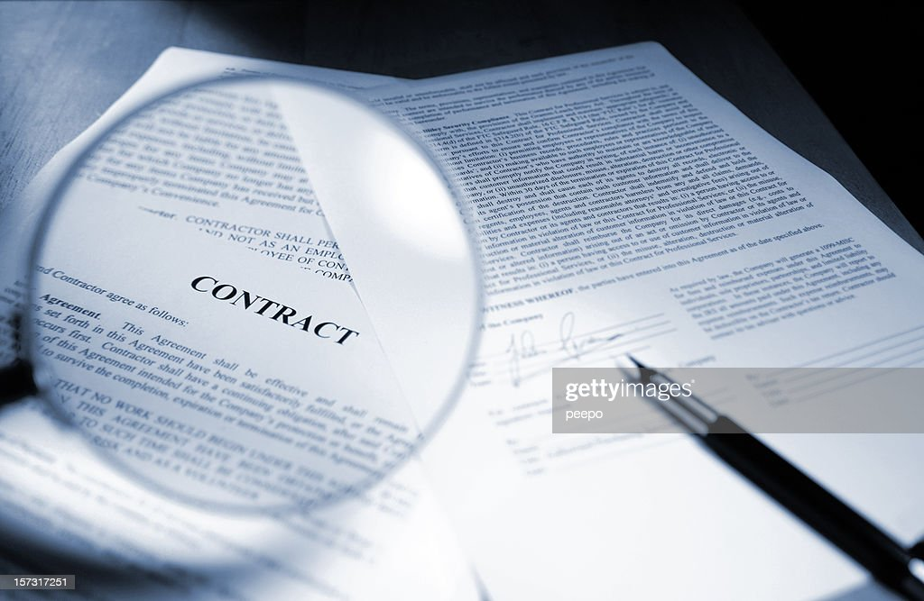 Magnifying Glass Examining Signed Legal Contract : Stock Photo