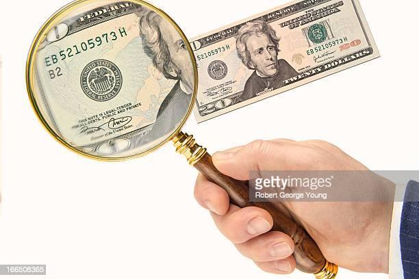 Magnifying glass examining US 20 dollar bill