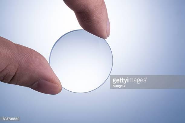 magnifying glass held between the fingers - getönt stock-fotos und bilder