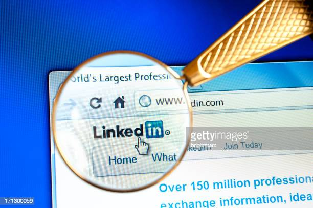 magnifying glass held over linkedin website - magnifying glass icon stock photos and pictures