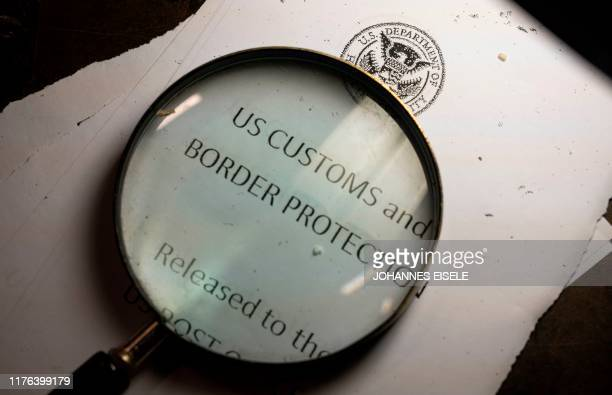 A magnifying glass is seen next to a logo of the Customs and Border Protection Trade and Cargo Division at John F Kennedy Airport's US Postal Service...