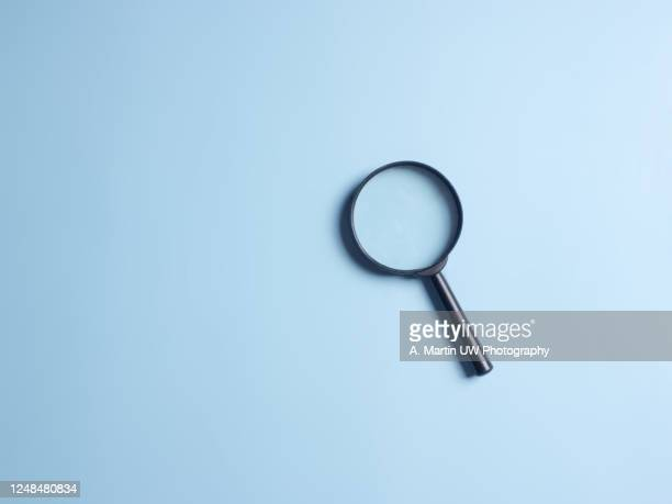 magnifying glass on blue colour background with copy space. searching information data concept - searching stock pictures, royalty-free photos & images