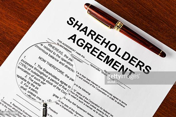 magnifying glass on shareholders agreement - shareholder stock pictures, royalty-free photos & images