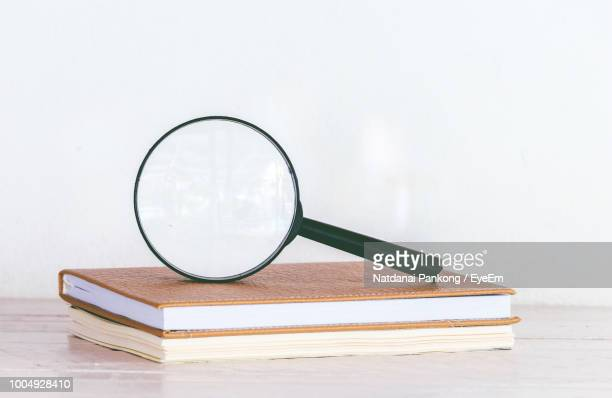 Magnifying Glass On Stack Books Against White Background