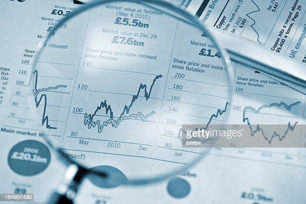 magnifying glass on stock price graphs from financial newspaper