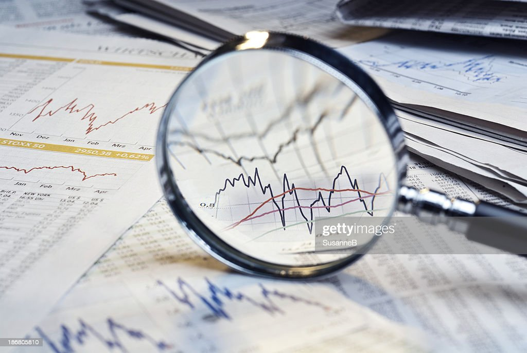 Magnifying glass on top of financial market info : Stock Photo