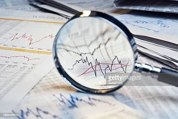 magnifying glass on top of financial market info - publication stock pictures, royalty-free photos & images