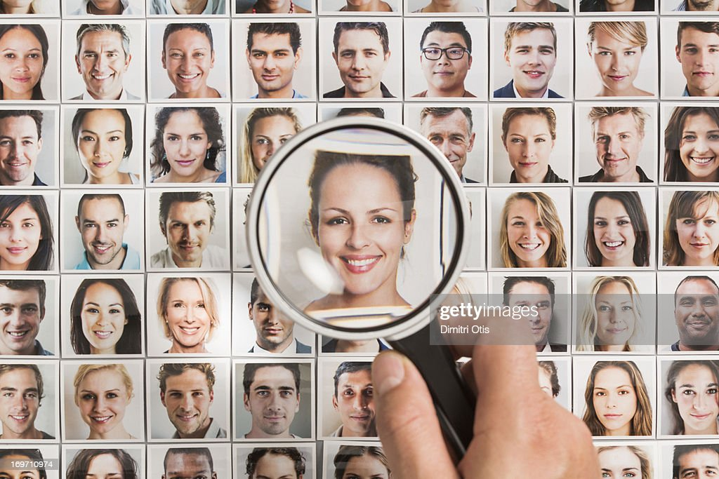 Magnifying glass on woman portrait amongst others : Stock Photo