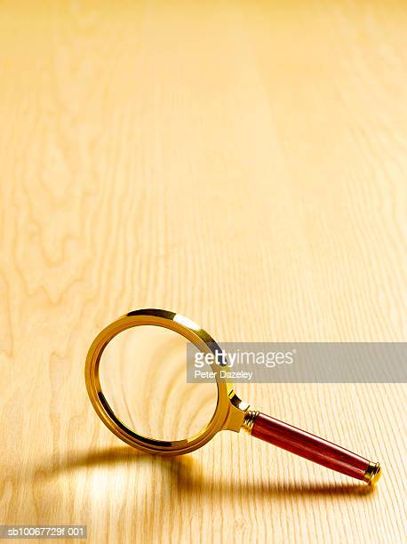 Magnifying glass on wooden floor, close-up