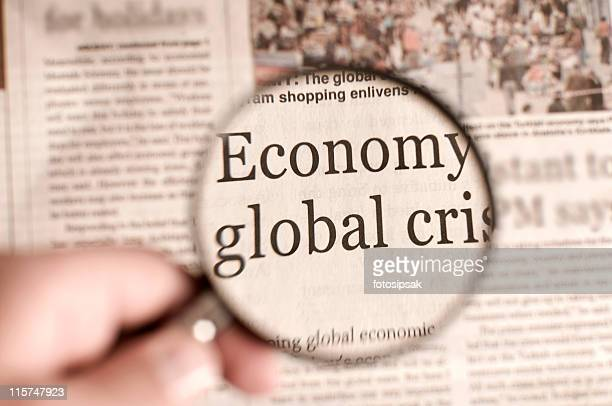 magnifying glass over a newspaper highlighting words - economy stock pictures, royalty-free photos & images