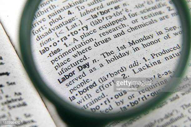 a magnifying glass showing the definition of labor day - labor day stock pictures, royalty-free photos & images