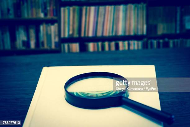 Magnifying Glass With Book On Table