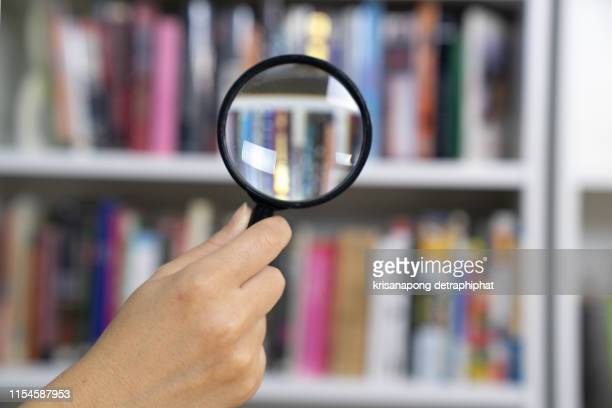 magnifying glass with books - 綴り ストックフォトと画像