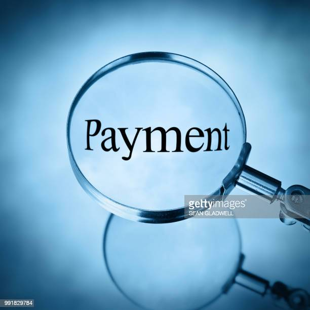 magnifying glass with the word payment magnified - wages stock pictures, royalty-free photos & images