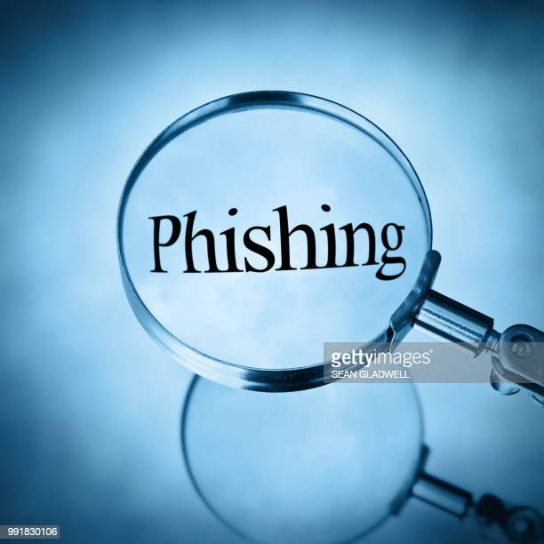 magnifying glass with the word phishing magnified - phishing stock pictures, royalty-free photos & images