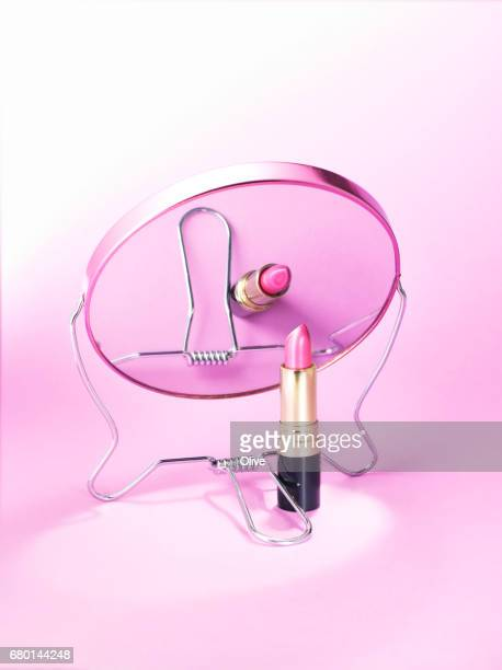 magnifying mirror on purple background with lipstick