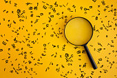 Magnifying With Wooden Alphabets Around On Yellow Background