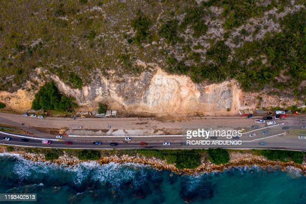 Cars drive through an area on highway 2 that was heavily affected by a landslide after after a powerful earthquake hit the island in Ponce Puerto...