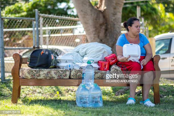 A woman sits on a sofa in a camp set up at a baseball field in Guanica Puerto Rico on January 11 after a powerful earthquake hit the island A 59...