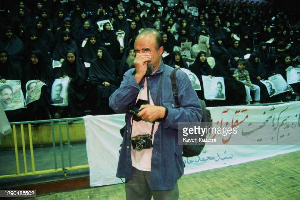 Magnum photographer of Iranian origin Abbas Attar, commonly known by his first name Abbas holds a magnifying lupe to his eye during a rally of...