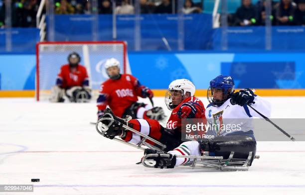 Magnus Bogle of Norway battles for the puck with Sandro Kalegaris of Italy in the Ice Hockey Preliminary Round Group A game between Norway and Italy...