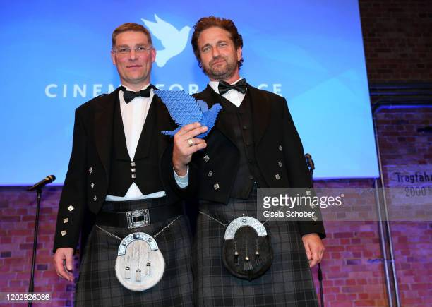 Magnus MacFarlane Barrow and Gerard Butler with award during the Cinema For Peace Gala at Westhafen Event & Convention Center on February 23, 2019 in...