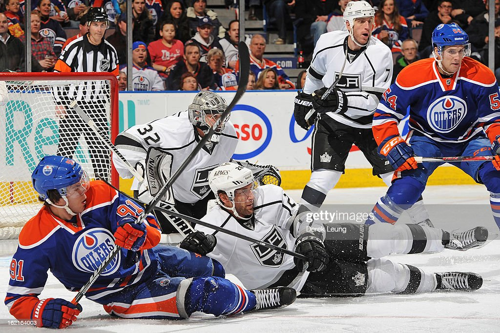 Magnus Paajarvi #91 of the Edmonton Oilers and Jarret Stoll #28 of the Los Angeles Kings fall in front of the net of Jonathan Quick #32 during an NHL game at Rexall Place on February 19, 2013 in Edmonton, Alberta, Canada. The Los Angeles Kings won 3-1.