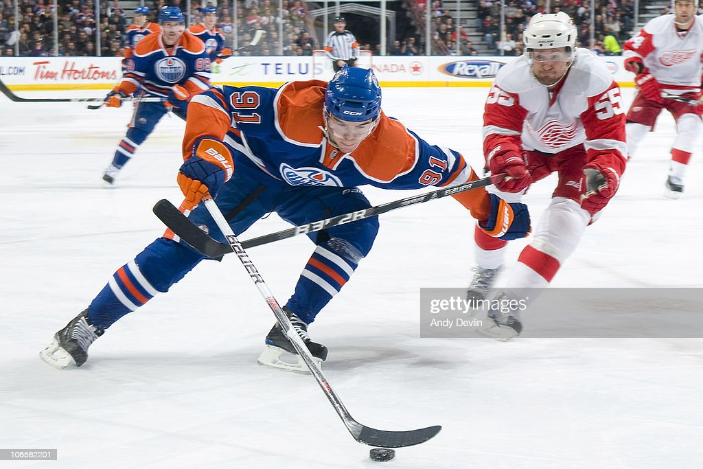 Magnus Paajarvi #91 of the Edmonton Oilers carries the puck past a defending Niklas Kronwall #55 of the Detroit Red Wings at Rexall Place on November 5, 2010 in Edmonton, Alberta, Canada.
