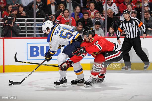 Magnus Paajarvi of the St Louis Blues approaches the puck as Viktor Svedberg of the Chicago Blackhawks reaches from behind in the first period of the...