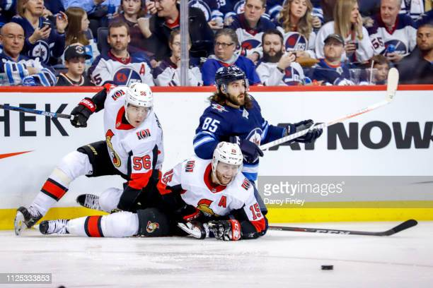 Magnus Paajarvi Zack Smith of the Ottawa Senators and Mathieu Perreault of the Winnipeg Jets lay on the ice after colliding along the boards during...