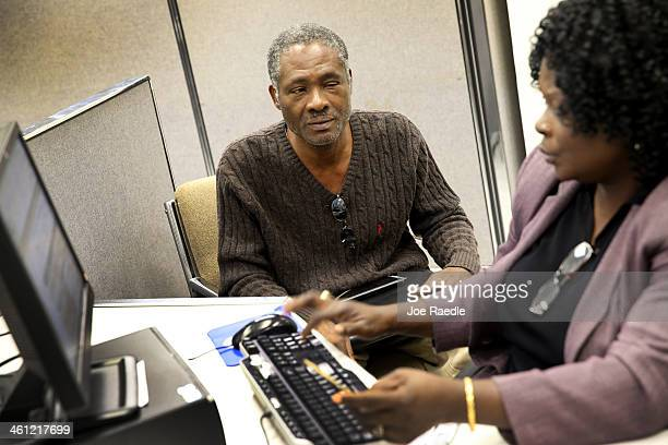 Magny Laguerre sits with career specialists Sidalouise Charlotin as she helps him fill out a form for unemployment benefits at a Workforce One...