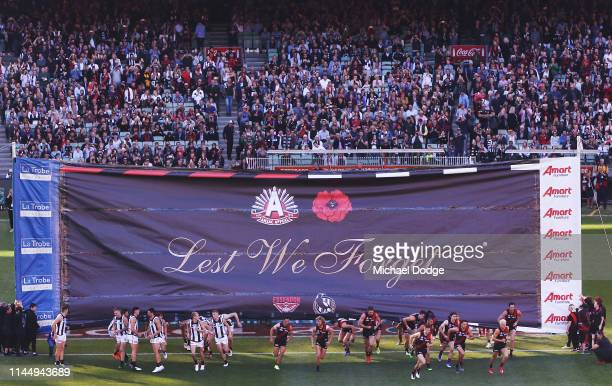 Magpies and Bombers teams break through the Anzac banner together during the round 6 AFL match between Essendon and Collingwood at Melbourne Cricket...