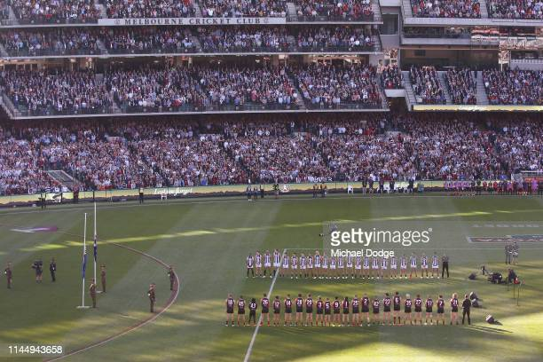Magpies and Bombers teams stand in line for a minutes silence during the ANZAC observance during the round 6 AFL match between Essendon and...