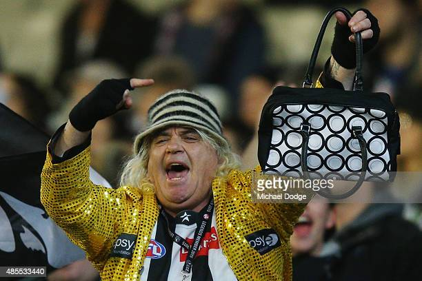 Magpies cheersquad leader Joffa Corfe holds up a handbag to Cats fans after he celebrates a goal during the round 22 AFL match between the Geelong...