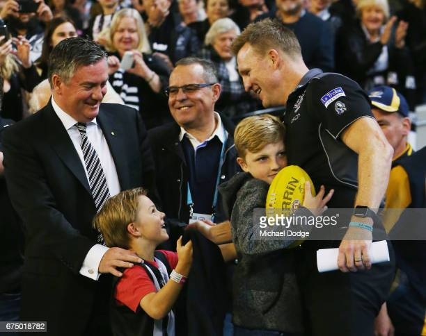 Magpies head coach Nathan Buckley celebrates the win with Magpies President Eddie Maguire as he is hugged by his son after their win during the round...