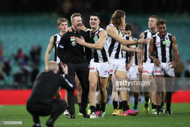 Magpies head coach Nathan Buckley celebrates victory with Brayden Maynard of the Magpies and team mates after the round 13 AFL match between the...