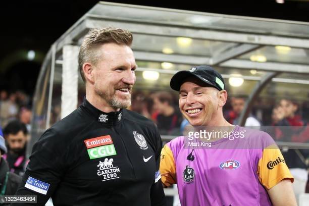 Magpies head coach Nathan Buckley celebrates victory with Magpies staff after coaching his final match for the Magpies during the round 13 AFL match...