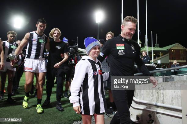 Magpies head coach Nathan Buckley celebrates victory with son Ayce Buckley after coaching his final game for the Magpies during the round 13 AFL...