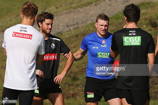 Magpies head coach Nathan Buckley geans Tim Broomhead by the arm while teaching players their positional moves on game day during a Collingwood...