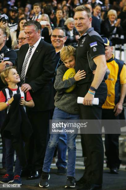 Magpies head coach Nathan Buckley is hugged by his son after their win during the round six AFL match between the Geelong Cats and the Collingwood...