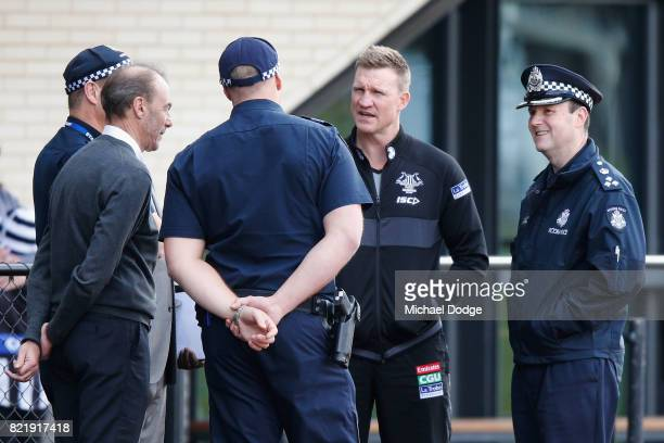 Magpies head coach Nathan Buckley is seen talking to Victorian Police officers who attended training to watch their colleagues train with players...