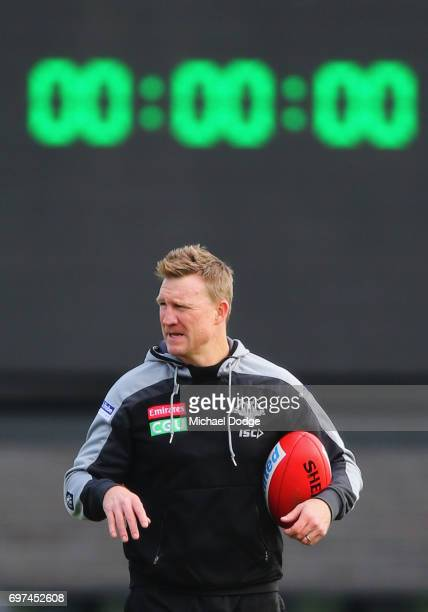 Magpies head coach Nathan Buckley looks upfield with the time clock behind him during a Collingwood Magpies AFL training session at Gosch's Paddock...