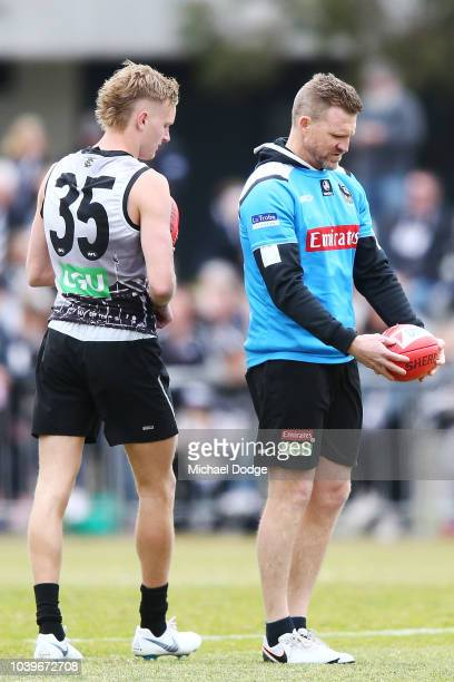 Magpies head coach Nathan Buckley practices the unusual ball grip of Jaidyn Stephenson of the Magpies before he kicks during a Collingwood Magpies...