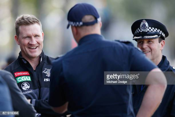 Magpies head coach Nathan Buckley reacts when talking to Victorian Police officers who attended training to watch their colleagues train with players...