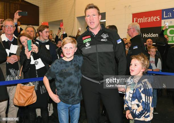 Magpies head coach Nathan Buckley sings the song in the rooms with his sons Jet and Ayce after winning the round nine AFL match between the...
